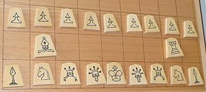 "Shogi - An example set of ""international"" pieces. In this set, those pieces that do not have their equivalents in chess have symbols that iconically show their movement (e.g. the silver general's crown and ribbons point towards its possible directions of movement)."