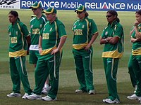 Six females in green cricketing outfits standing on the outfield looking at the presentation stage