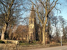 Victorian Gothic Revival church with spire among trees