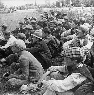 Stara Gradiška concentration camp - Prisoners seated in a field in the camp.