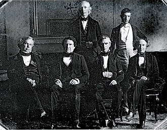 James K. Polk - Polk and his cabinet in the White House dining room, 1846. Front row, left to right: John Y. Mason, William L. Marcy, James K. Polk, Robert J. Walker. Back row, left to right: Cave Johnson, George Bancroft. Secretary of State James Buchanan is absent. This was the first photograph taken in the White House, and the first of a presidential Cabinet.