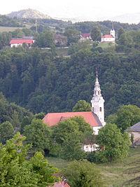 Stopiče - cerkev Marije Tolažnice, v ozadju G. Težka Voda in hrib Breznik.jpg