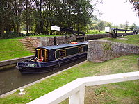 Narrow boat (named Toad) emerging from lock with black gates and white ends of the gate arms. Around the lock is a grassy area.