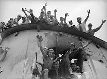 Close up of a ship's funnel, which has a large hole in the side. Sailors are smiling and waving at the photographer from the top of the funnel and inside the hole.