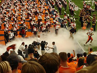 "Syracuse Orange football - Former football head coach Greg Robinson ""chases"" the last of his players onto the field before the kickoff of his inaugural 2005 season. It was also the first game played on the Carrier Dome's new FieldTurf."