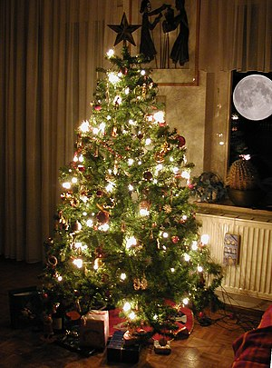 Artificial Christmas tree - A PVC Christmas tree decorated with fairy lights and baubles
