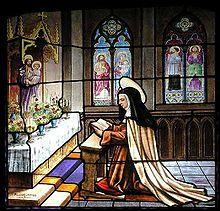 Vitrail coloré montrant Thérèse en prière sur un prie-Dieu dans une chapelle.