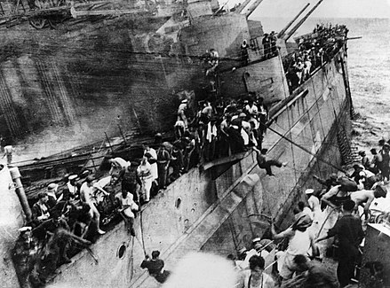 The crew of the sinking Prince of Wales abandoning ship to the destroyer Express. Moments later, the list on Prince of Wales suddenly increased and Express had to withdraw. Observe the barrels of the 5.25 in guns, which were unable to depress low enough to engage attackers due to the list. The Sinking of HMS Prince of Wales by Japanese Aircraft Off Malaya, December 1941 HU2675.jpg