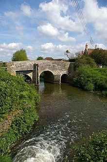 Three arch stone bridge over water.