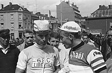 Photographie montrant deux cyclistes en conversation, entourés par la foule, au départ d'une course.