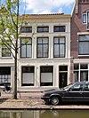 foto van Pand met verdieping en mezzanino onder met pannen gedekt schilddak, en voorzien van een midden 19e-eeuwse, witgepleisterde lijstgevel