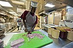 U.S. Navy Culinary Specialist Seaman Isaiah Harris chops ham in the galley of the guided missile destroyer USS Arleigh Burke (DDG 51) March 8, 2014, in Marseille, France 140308-N-WD757-009.jpg