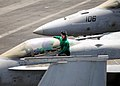 U.S. Sailor sits on an F-A-18C Hornet assigned to Strike Fighter Squadron (VFA) 151 on the flight deck of the aircraft carrier USS Abraham Lincoln (CVN 72) in the Persian Gulf.jpg
