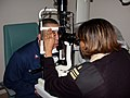 US Navy 040128-N-8861F-001 Hospital Corpsman 2nd Class Jamie Zhunepluas from Queens, N.Y., gets a slit lamp eye exam by Lt. Cmdr. Jacqueline Pierre from Shelbyville, Texas.jpg