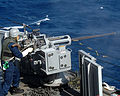 US Navy 041210-N-2970T-003 Gunner's Mate Seaman Daniel A. Wright fires an Mk-38 25mm machine gun during a general quarters (GQ) drill aboard the dock landing ship USS Fort McHenry (LSD 43).jpg