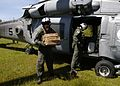 US Navy 050107-N-5376G-006 Aviation Warfare System Operator 2nd Class Cory Merritt, left, and Aviation Warfare System Operator 2nd Class Geoff Larson unload food and water in the town of Meulaboh, Sumatra, Indonesia.jpg