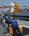 US Navy 050415-N-5526M-010 Sailors aboard the Arleigh Burke-class guided missile destroyer USS Mustin (DDG 89), release chains holding pallet of stores sent over from the fast combat support ship USS Camden (AOE-2) during a rep.jpg