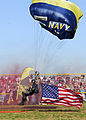 US Navy 070417-N-2903M-013 Chief Special Warfare Operator Larry Summerfield of the Navy Parachute Team delivers the American flag to the football field during a performance at North Bullitt High School.jpg