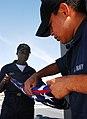 US Navy 090112-N-9698C-020 Storekeeper Seaman Apprentice Josiah Thomas and Storekeeper Seaman Recruit Porsha Corley, fold the Ensign aboard the guided-missile destroyer USS Hopper (DDG 70).jpg