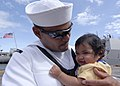 US Navy 090921-N-2456S-100 Sonar Technician (Surface) 3rd Class Frank Diaz assigned to the guided-missile destroyer USS Bainbridge (DDG 96) holds his four-month old son for the first time following his return home to Naval Stat.jpg