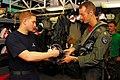 US Navy 090929-N-2918M-030 Aircrew Survival Equipmentman 2nd Class Steven Martin, left, hands Lt. Cmdr. Kevin McGee his flight helmet after a pre-flight inspection.jpg