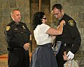 US Navy 100625-N-5346R-003 The wife of Police Officer Anthony Capellupo pins is badge to his uniform as his son looks on.jpg