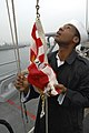 US Navy 101013-N-6477M-275 Seaman Mario Curtis prepares to raise the Navy Jack for morning colors aboard the amphibious transport dock ship USS Cle.jpg
