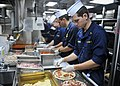 US Navy 101204-N-5838W-002 Officers assigned to the guided-missile destroyer USS Mason (DDG 87) prepare pizza in the ship's galley.jpg