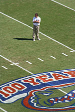 Urban Meyer, standing on the field with his arms folded