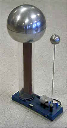 Large metal sphere suppported on a clear plastic column, inside of which a rubber belt can be seen.  A smaller sphere is supported on a metal rod. Both are mounted to a baseplate, on which there is a small driving electric motor.