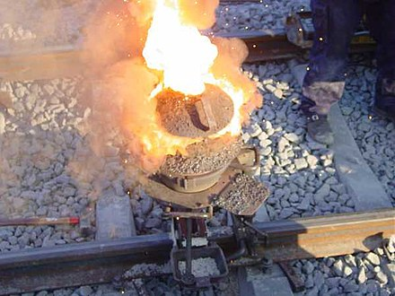 Thermite reaction proceeding in railway welding. Shortly after this, the liquid iron flows into the mould around the rail gap Velp-thermitewelding-1.jpg