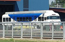 A single train car, painted blue and white, sits on a track between a metal fence and a large blue building.