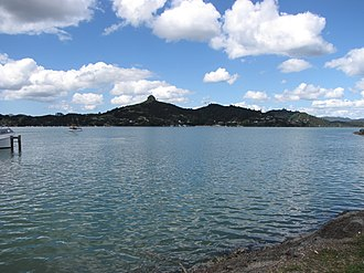 Whangaroa Harbour - The settlement of Whangaroa, with the volcanic plug of St Paul's Rock rising over it