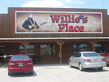 "A store with a sign that reads ""Willie's Place"". The apostrophe is replaced in the sign by a bullet hole, the structure of the store is constructed in wooden with three columns. There are four windows and there are a red and a grey car in the parking lot."