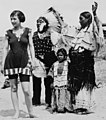 Woman in swimsuit on beach with an Indian family in 1923- LCCN99471588 (cropped).jpg