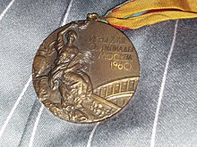 A bronze colored medal with a woman wearing a toga on the left side. On the right there is Cyrillic writing.