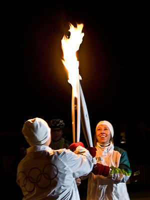 The Olympic Flame passes from one torch to ano...