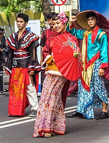 Students in Chinese fusion clothing holding a parasol and smiling