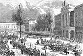 Gravură care descrie parada trupelor belgiene în fața Palatului Regal.  Grupuri călare și infanterie merg în succesiune rapidă.