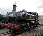 A pannier tank locomotive is seen from the front and to the right and is standing over an ash pit. It is all in black apart from a number of small details. The buffer beam at the front is red. The locomotive number, 9600, is shown in white on a plate on the smokebox door and on a larger plate, edged in white, on the side of the cab. There is a small yellow disc, with the letter C above the number plate. The shed number, 84 E, is shown in white on a small plate near the bottom of the smokebox door. The pannier tank and cab side are lined in red and white, and the British Railways crest, in yellow, white and red, is on the side of the pannier. The letters T Y S are shown in white on the running plate step near the front. The coupling rods are unpainted and are steel grey. Finally, two white lamps are stored next to the black toolbox near the back of the running plate.