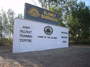 A sign stands surrounded by bushland. It features the Army's Rising Sun badge and reads: Blamey Barracks / Army Recruit Training Centre / Kapooka Military Area / Home of the Soldier.