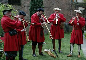 Sackbut - A re-created wait, an ensemble of loud instruments suited to playing outdoors. Centre, a sackbut.