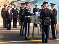 A delegation of United Nations Command Military Armistice Commission (UNCMAC) officials look on as the UNCMAC Honor Guard drapes the United Nations flag over the transfer case of what is believed to be one 981009-F-FC975-502.jpg