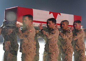 Canadian Armed Forces - Canadian Armed Forces personnel carry the coffin of a comrade who was killed onto an aircraft at Kandahar Air Field, 1 February 2009