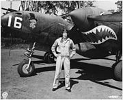 Man standing in front of a twin-propeller aircraft