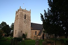 Church with substantial tower under a sky of duck-egg blue, with a large Yew on the right., a very dark green.  The tower is broad, but barely higher than the deeply pitched roof on the nave.  It has a clockface on the nearest side.