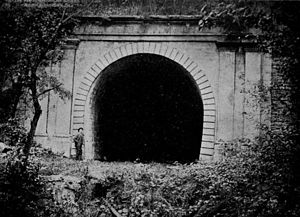 Staple Bend Tunnel - View of the abandoned tunnel, ca. 1911. A man stands to the left for a height comparison.