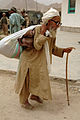 An Afghan elder carries his load of supplies he received at a Village Medical Outreach (VMO) site held at the Panjwai Province on June 4, 2006 060604-A-KP131-012.jpg