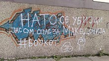 "White spray painted text on a tan wall that reads ""НАТО СЕ УБИЈЦИ ЈАС СУМ СПАС ЗА МАКЕДОНИЈА #БОЈКОТ"" which translates to ""NATO are killers. I am for the salvation of Macedonia. #Boycott."""