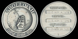 Apollo 12 mission emblem and crew names (front). Dates (launch, lunar landing, and return), and serial number 1 (back)